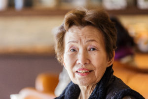 Older Asian American Woman Smile at a camera