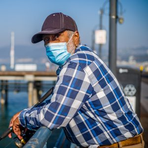 An older man leans on the Santa Monica Pier.