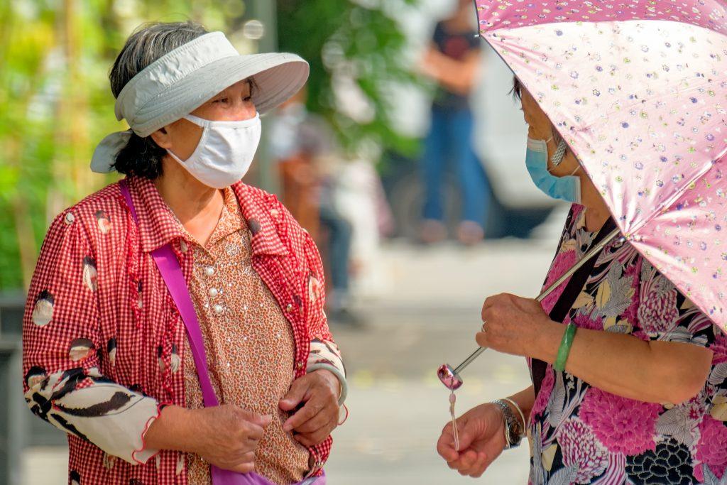 Image of two older masked women talking