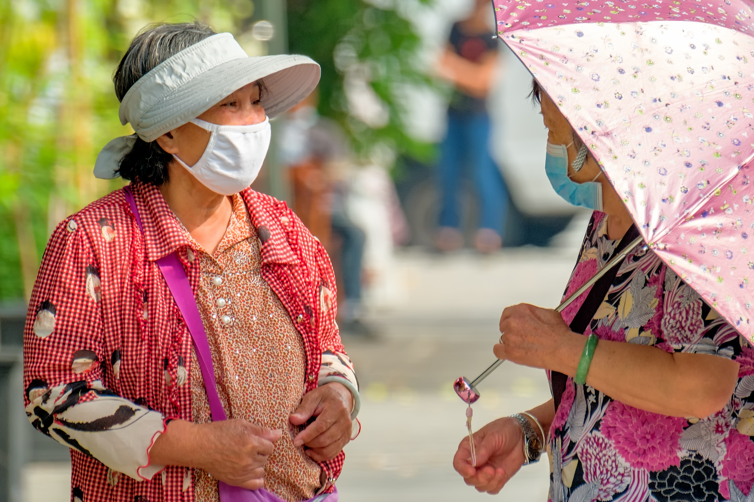 Image of two older masked women talking